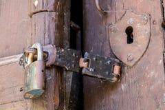 Fermez-vous du cadenas et du vieux loquet sur une vieille porte en bois photo stock