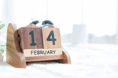 Fermez-vous du calendrier en bois montrant le jour de la valentine entouré avec le soleil léger chaud Événement de Saint Valentin Photos stock