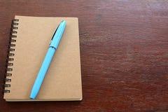 Fermez-vous du carnet vide et du stylo bleu sur la table en bois, foyer sélectif pour l'espace de copie photographie stock libre de droits