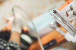 Fermez-vous du centre sélectif de l'ensemble d'outils de matériel médical du ` s de dentiste en métal à un arrière-plan brouillé images stock