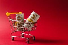 Fermez-vous du chariot de poussée d'épicerie de supermarché pour faire des emplettes avec les éléments en plastique jaunes sur la image stock