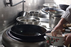 Fermez-vous du chef travaillant préparant la nourriture chinoise photo stock