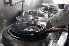 Fermez-vous du chef travaillant préparant la nourriture chinoise image stock