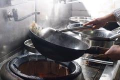 Fermez-vous du chef travaillant préparant la nourriture chinoise images stock