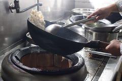 Fermez-vous du chef travaillant préparant la nourriture chinoise photographie stock