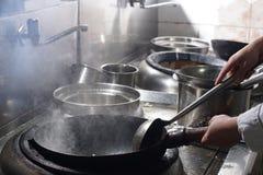 Fermez-vous du chef travaillant préparant la nourriture chinoise photos libres de droits
