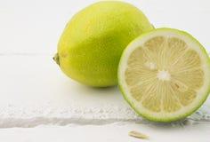 Fermez-vous du citron entier et de la moitié sur le bois blanc rustique b Photo stock