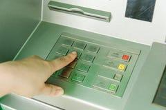 Fermez-vous du code entrant de mot de passe de main de l'homme sur la machine de banque d'atmosphère Photographie stock