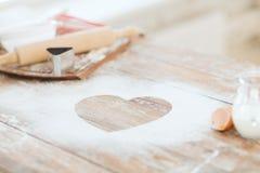 Fermez-vous du coeur de la farine sur la table en bois à la maison Photographie stock libre de droits