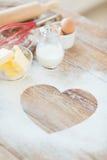 Fermez-vous du coeur de la farine sur la table en bois à la maison Images libres de droits