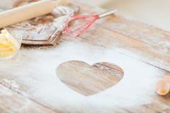 Fermez-vous du coeur de la farine sur la table en bois à la maison Image libre de droits
