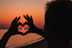 Fermez-vous du coeur fait par le fond de mains de femelle la mer de coucher du soleil photos de style d'effet de vintage Images libres de droits