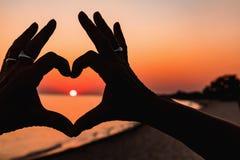 Fermez-vous du coeur fait par le fond de mains de femelle la mer de coucher du soleil photos de style d'effet de vintage Image libre de droits