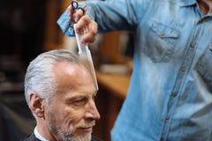 Fermez-vous du coiffeur peignant les cheveux supérieurs de client Photographie stock libre de droits