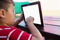 Fermez-vous du comprimé numérique émouvant de garçon tout en se reposant à la table image libre de droits