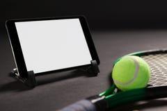 Fermez-vous du comprimé numérique par la raquette et la boule de tennis photo stock