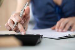 Fermez-vous du comptable ou du banquier féminin effectuant des calculs Photos stock