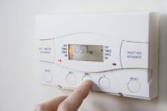 Fermez-vous du contrôle d'arrangement de main pour la chauffage et l'eau chaude Photos libres de droits