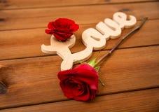 Fermez-vous du coupe-circuit d'amour de mot avec la rose de rouge sur le bois Image stock