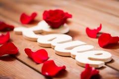 Fermez-vous du coupe-circuit d'amour de mot avec la rose de rouge sur le bois Image libre de droits
