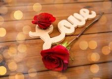 Fermez-vous du coupe-circuit d'amour de mot avec la rose de rouge sur le bois Photographie stock libre de droits