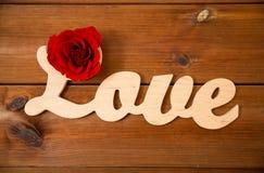 Fermez-vous du coupe-circuit d'amour de mot avec la rose de rouge sur le bois Photos stock