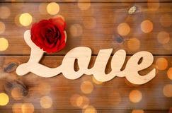 Fermez-vous du coupe-circuit d'amour de mot avec la rose de rouge sur le bois Images stock