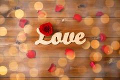 Fermez-vous du coupe-circuit d'amour de mot avec la rose de rouge sur le bois Photos libres de droits