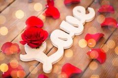 Fermez-vous du coupe-circuit d'amour de mot avec la rose de rouge sur le bois Photo stock