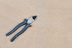 Fermez-vous du coupeur de fil manipulé noir sur le fond en bois Image libre de droits