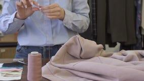 Fermez-vous du couturier féminin, qui coud le bouton sur la robe dans le studio lumineux banque de vidéos