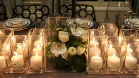 Fermez-vous du décor et des bougies de fleur sur la table de dîner image libre de droits