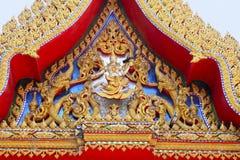 Fermez-vous du découpage rouge d'or Le temple orne admirablement les découpages en bois dépeignant la vie de Bouddha familiarisée photos stock