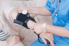 Fermez-vous du docteur féminin vérifiant la pression du patient plus âgé images stock