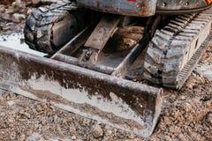 Fermez-vous du fonctionnement de bouteur avec le sol sur le chantier de construction image libre de droits
