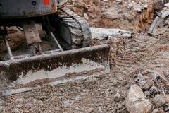 Fermez-vous du fonctionnement de bouteur avec le sol sur le chantier de construction photo stock