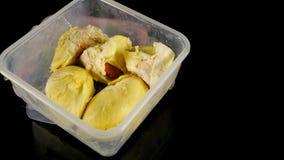 Fermez-vous du fruit crémeux de durian à l'intérieur du récipient en plastique dans le noir images libres de droits