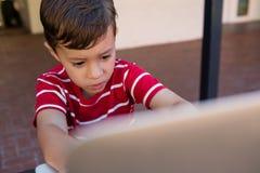 Fermez-vous du garçon à l'aide de l'ordinateur portable tout en se reposant sur la chaise photo libre de droits