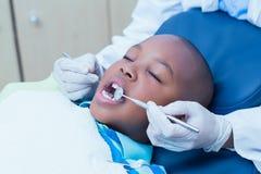 Fermez-vous du garçon faisant examiner ses dents photographie stock libre de droits