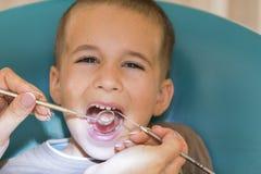 Fermez-vous du garçon faisant examiner ses dents par un garçon beau du dentiste A à l'hygiène d'Oral de dentiste photographie stock libre de droits