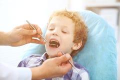 Fermez-vous du garçon faisant examiner ses dents par un dentiste photographie stock libre de droits