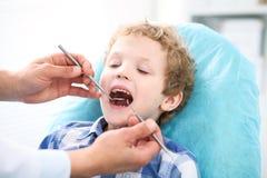 Fermez-vous du garçon faisant examiner ses dents par un dentiste photos stock