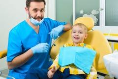 Fermez-vous du garçon faisant examiner ses dents par un dentiste photo libre de droits