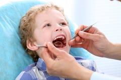 Fermez-vous du garçon faisant examiner ses dents par un dentiste images libres de droits