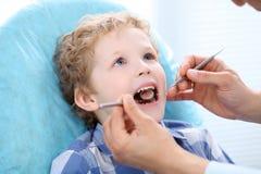 Fermez-vous du garçon faisant examiner ses dents par un dentiste Image libre de droits
