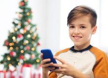 Fermez-vous du garçon heureux avec le smartphone à Noël Photographie stock