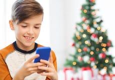 Fermez-vous du garçon heureux avec le smartphone à Noël Images libres de droits