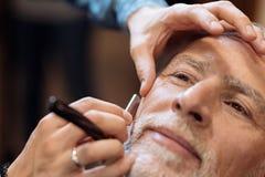 Fermez-vous du gentil homme supérieur étant rasé au raseur-coiffeur Photos stock