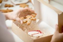 Fermez-vous du gingerman d'emballage de main de confiseur dans une boîte photos stock