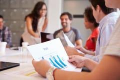 Fermez-vous du graphique de Looking At Profit d'homme d'affaires lors de la réunion Photos stock